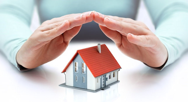 Hands protecting a home concept